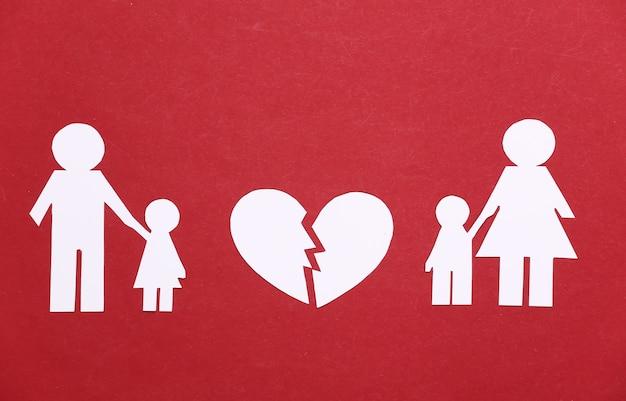 Broken family, divorce. split paper family, broken heart on a red