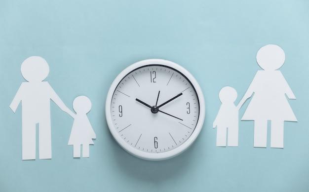Broken family, divorce. split paper family, clock on blue