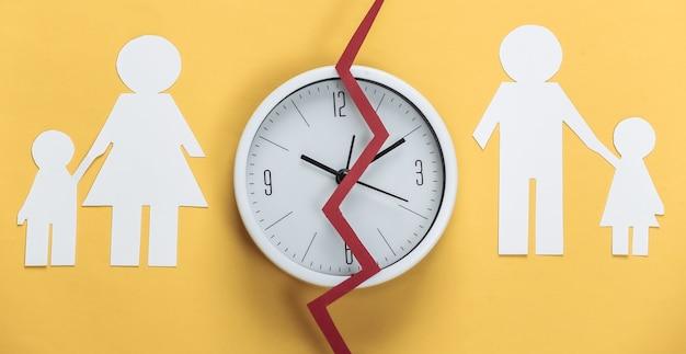 Broken family, divorce. split paper family, clock on yellow