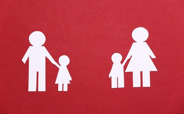 Broken family, divorce. split paper family on a red