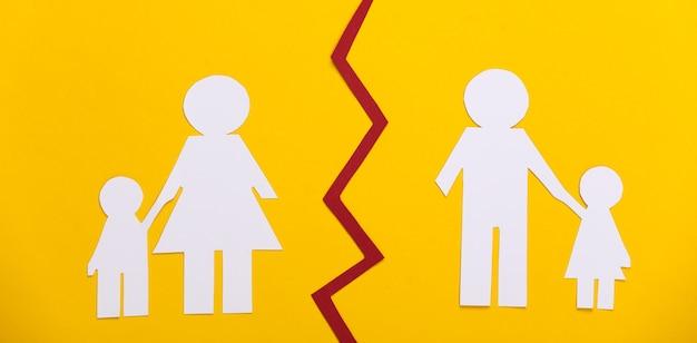 Broken family, divorce. split paper family on yellow