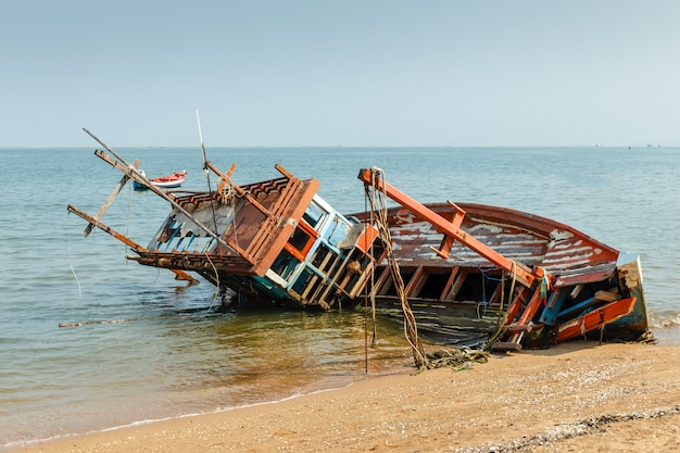 A broken fishing ship lies on its side near the shore, shipwrecked