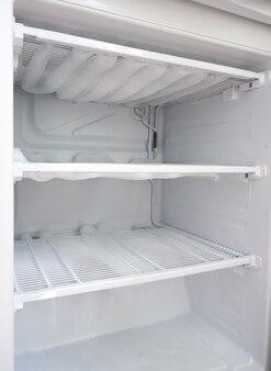 Сломанный холодильник. снег на полках морозильных камер. размораживание холодильника.