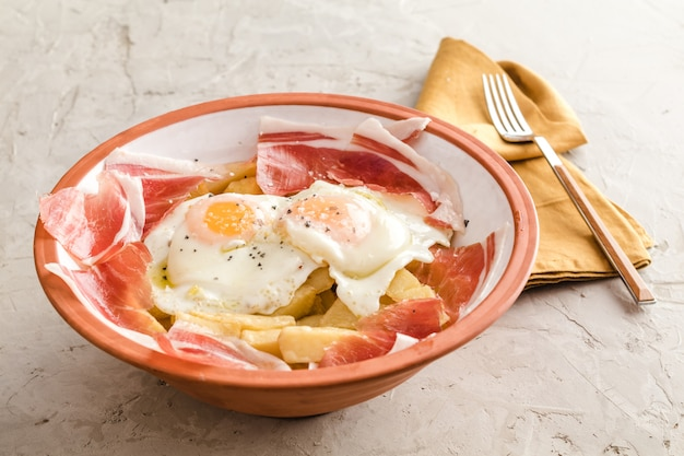 Broken fried eggs with potatoes and iberian cured ham