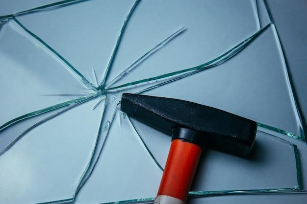 白で隔離あなたのイメージの壊れたガラスの背景。ハンマーで打撃から散らばった多くの大きな破片。