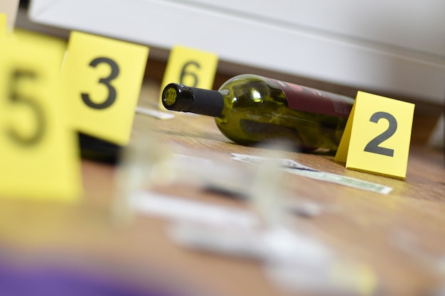 Broken glass and bottle of wine marked as evidence during crime scene investigation. many yellow markers with numbers