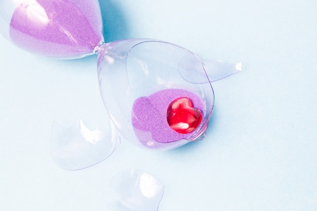Broken glass hourglass and a small red glass heart