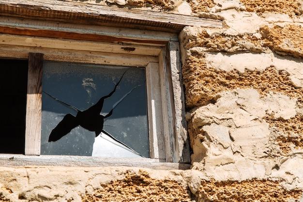 Битое стекло в окне здания. жилищные проблемы.
