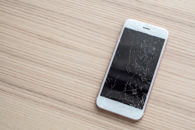Broken glass of mobile phone screen on wooden table
