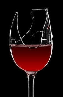 黒に分離された赤ワインの割れたガラス