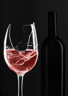 背景にボトルと赤ワインの割れたガラス