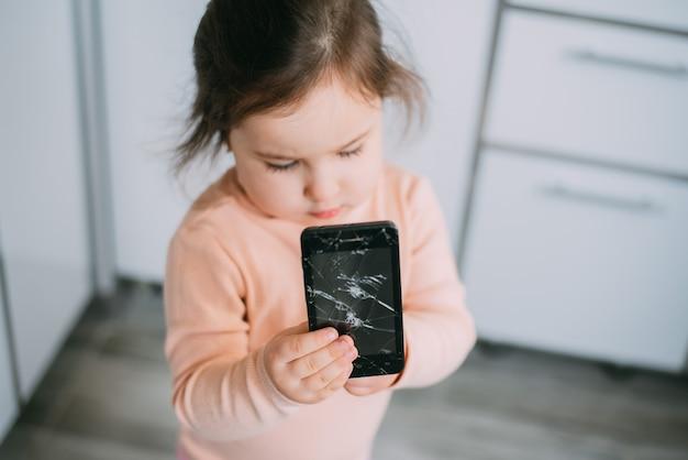 自宅のキッチンで欲求不満の女の子の手に壊れたガラスのスマートフォンの画面