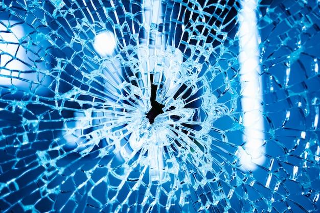Broken glass window. blue background. closeup.