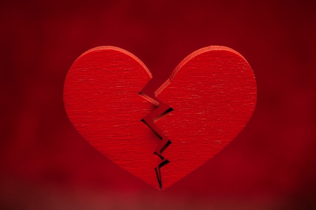 Broken heart. crack in the red heart, breaking the relationship. red background.