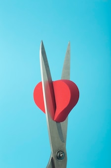 Broken heart cut with scissors on a colored background. unhappy love