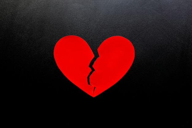 Broken heart made from red paper on black background, represent love.