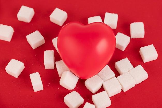 빨간 배경에 각설탕과 주사기로 만든 상한 마음. 당뇨병 개념입니다. 위에서 볼 수 있습니다. 공간을 만듭니다.