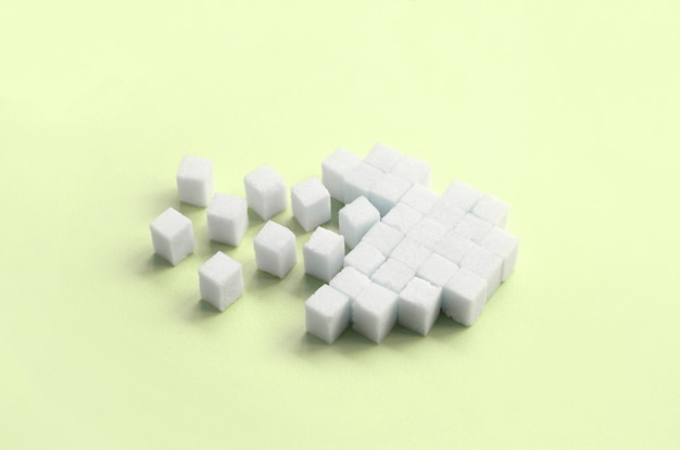 A broken heart made of sugar cubes lies on a trendy pastel lime