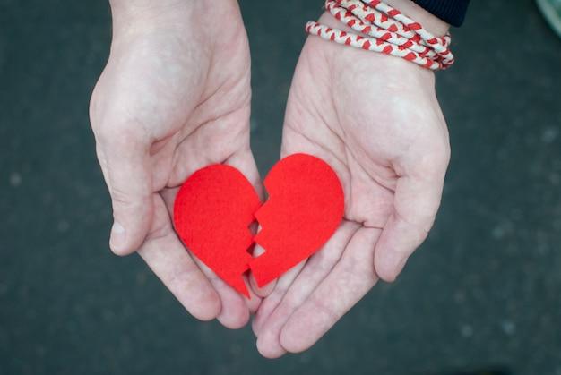 Broken heart in the male hands.