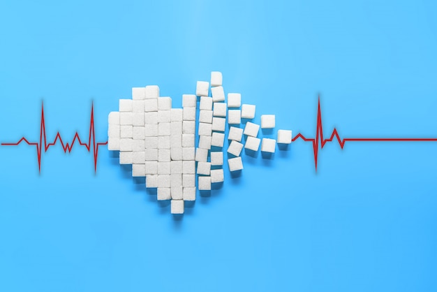 Broken heart of pure white sugar cubes on a blue background