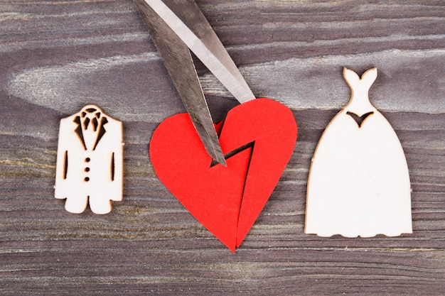 Broken heart with scissors. divorse and heartbreak concept. grey wood background.
