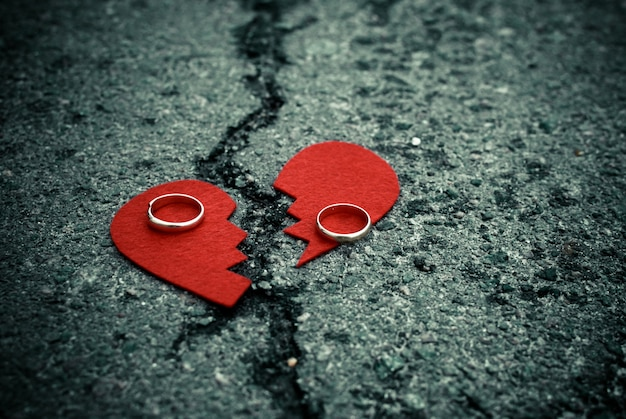 Broken heart with wedding rings on cracked asphalt