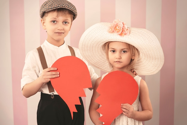 Broken hearted kid couple with a paper heart
