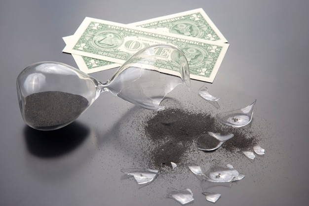 Broken hourglass on the of banknotes