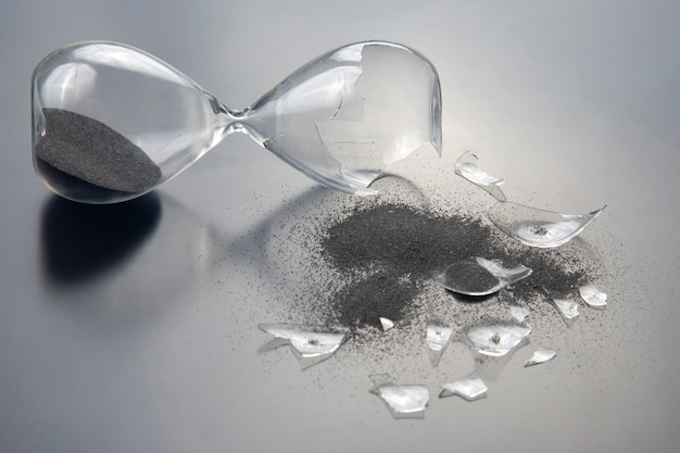 Broken hourglass shattered hope.