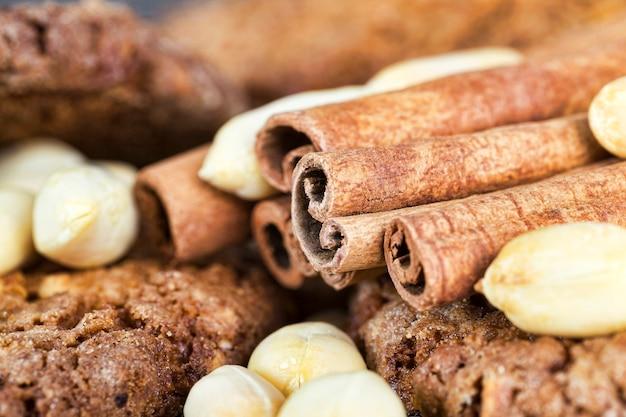 Разбитое на половинки и куски восхитительное и хрустящее овсяное печенье из муки, овсяных хлопьев и орехов, арахиса и корицы, домашнего приготовления