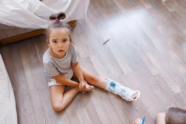 子供がマーカーで女の子に石膏を塗る骨への骨折した足の損傷