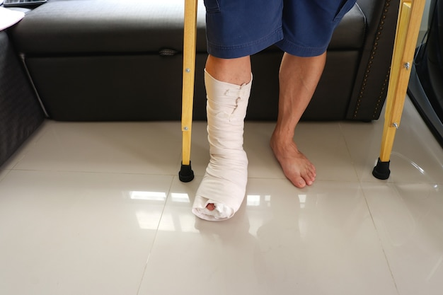 足の骨折した男と木製の松葉杖が自宅のソファに座っていた低断面図とコピースペースでクローズアップショット
