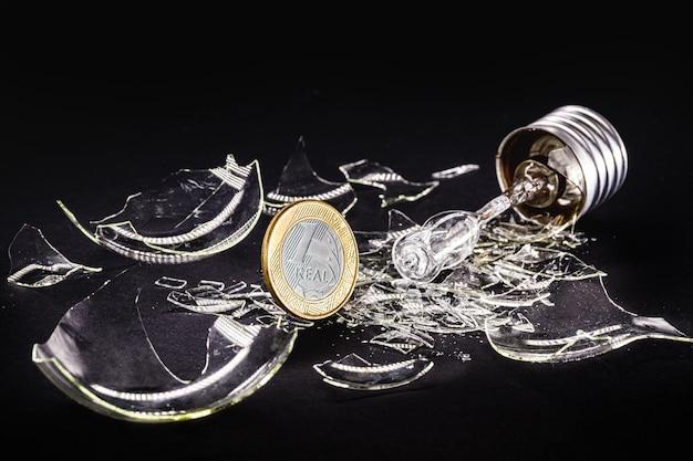 1つの本物のコイン、ブラジルのエネルギー危機または電気代の上昇の概念と黒の背景に壊れた電球