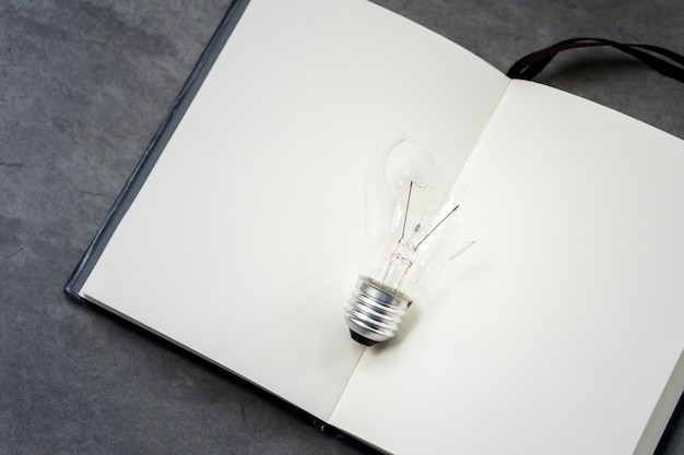 Broken lightbulb on book background, bad idea concept, solution