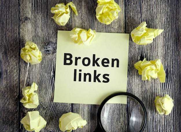 Broken links - text on yellow note sheets on a dark wooden background with crumpled sheets and a magnifying glass