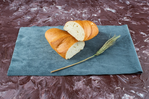 Сломанный буханка белого хлеба с колосом пшеницы на светлой предпосылке.