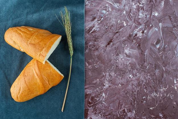 Pagnotta rotta di pane bianco con spiga di grano su uno sfondo chiaro.