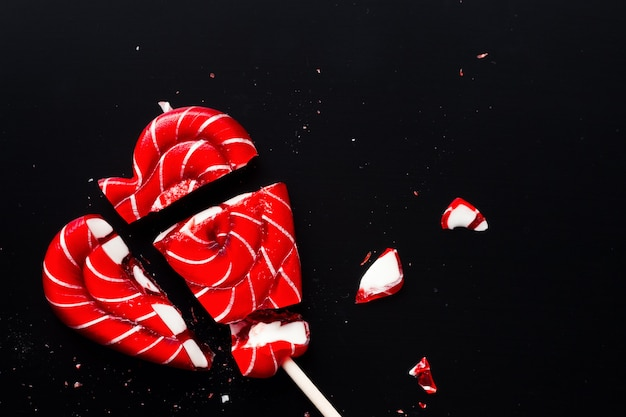 Broken lollipop in shape of heart on a dark background with copy space