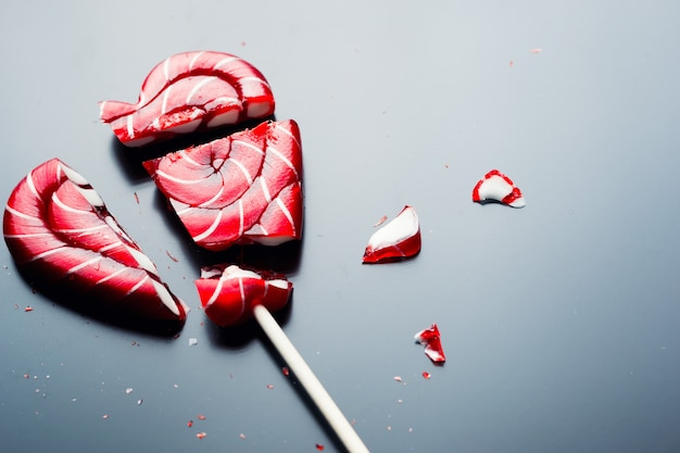 Broken lollipop in shape of heart on a dark background