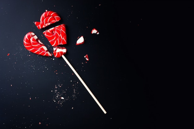 Broken lollipop in shape of heart on dark with copy space