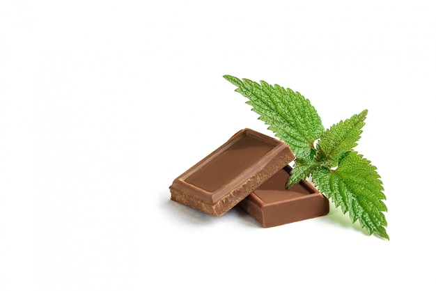 Broken milk chocolate and mint isolated on white background