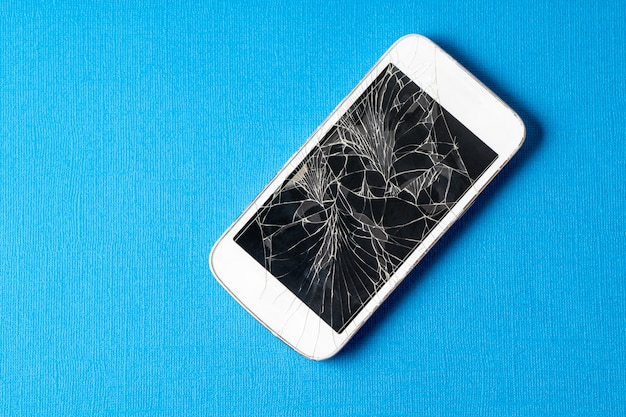 Broken mobile phone with cracked display on a blue background.