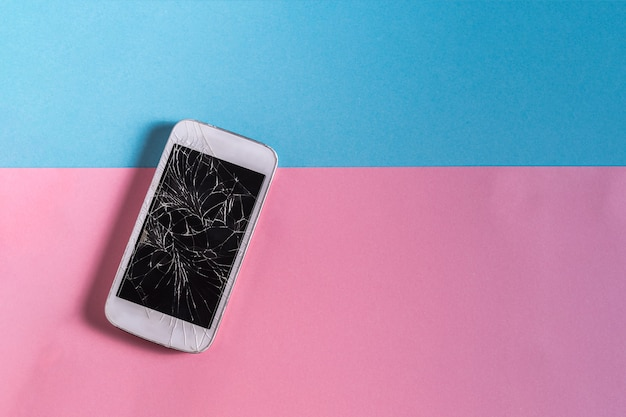Broken mobile phone with cracked display on blue and pink paper