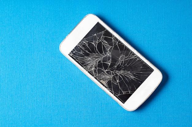 青い紙の背景にひびの入ったディスプレイ、フラットレイと壊れた携帯電話。