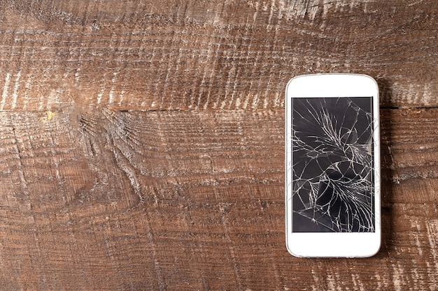 茶色の木製の背景、平らな横にひびの入ったディスプレイと壊れた携帯電話。