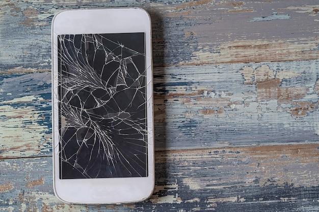 木製の青い背景、平らな横にひびの入ったディスプレイと壊れた携帯電話。