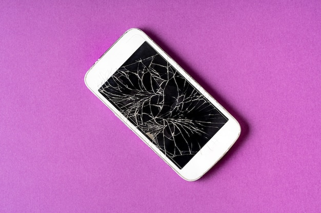 Broken mobile phone with cracked display on purple background.