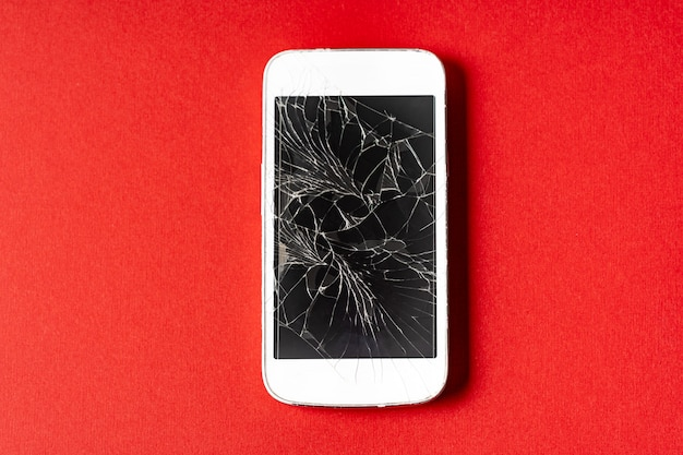 Broken mobile phone with cracked display on red background.