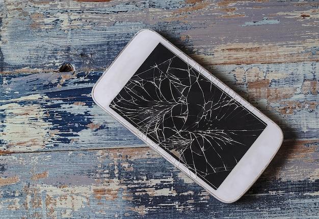 Сломанный мобильный телефон с треснувшим дисплеем