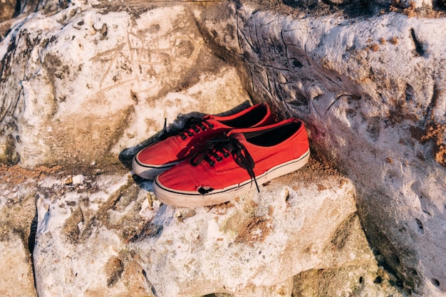 Broken old red shoes on a rock at sea coast